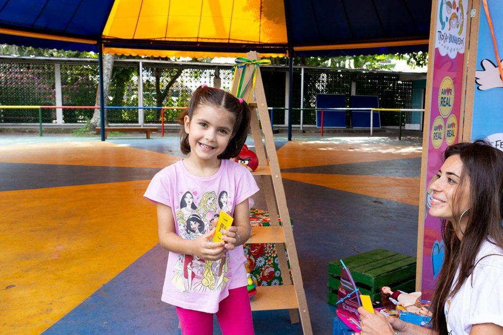Troca de brinquedos menina de rosa sorrindo