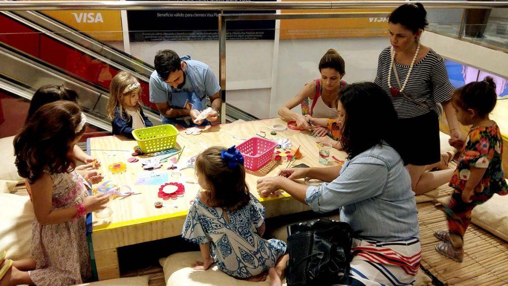 mesa com crianças fazendo flores